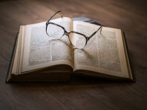 Picture of an open Bible with eyeglasses lying on top.